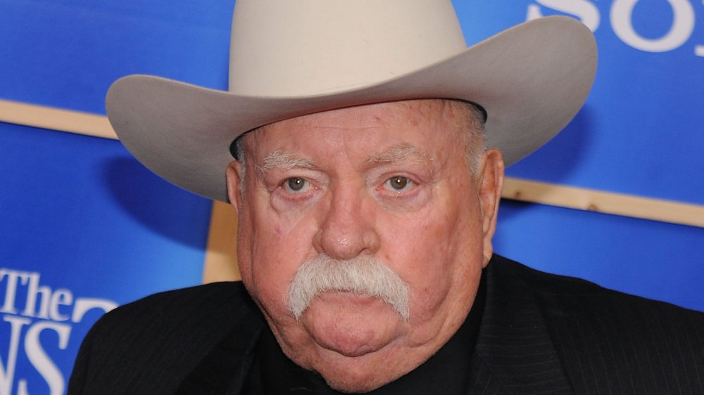 Wilford Brimley in a black suit and tan cowboy hat