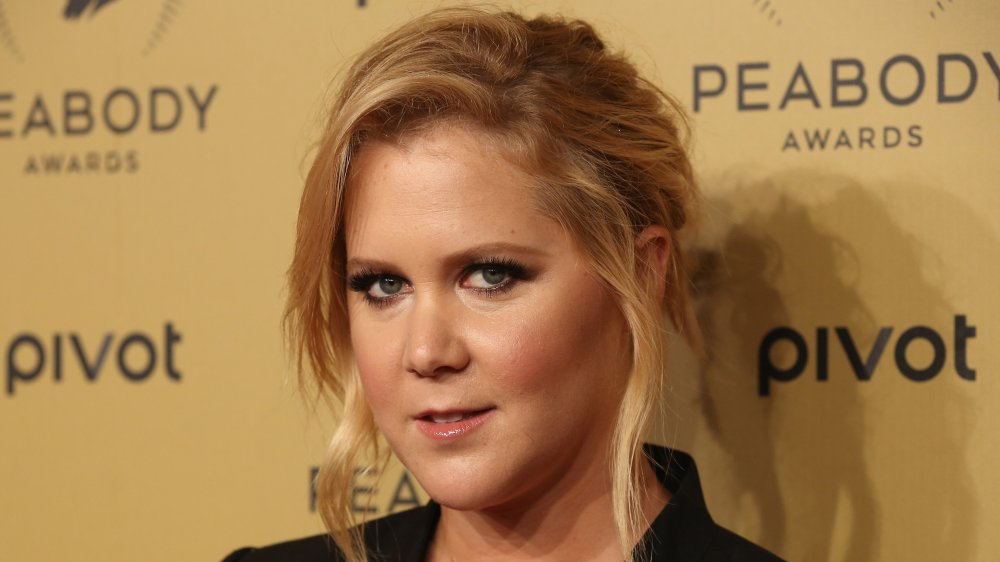 Amy Schumer in a black blazer with her hair in an up-do, posing with a small smile at the Peabody Awards