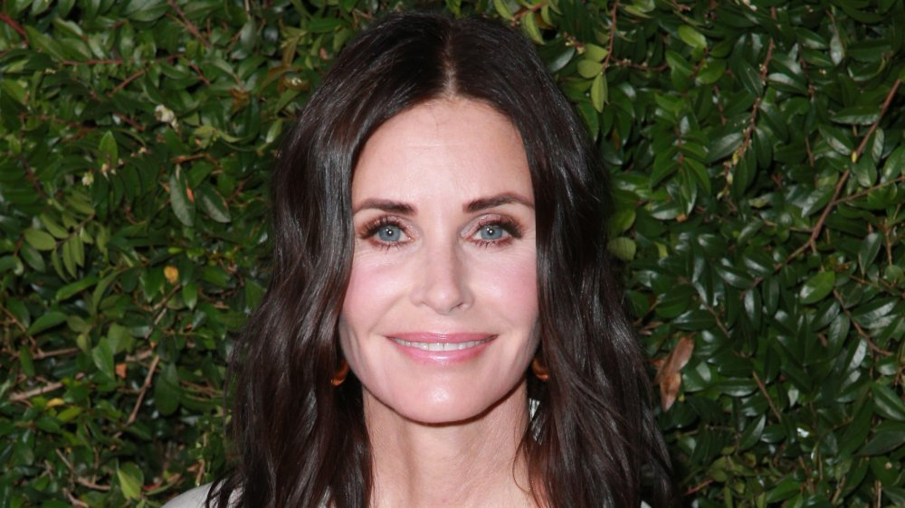 Courteney Cox in a white-and-black dress, smiling at an outdoor event