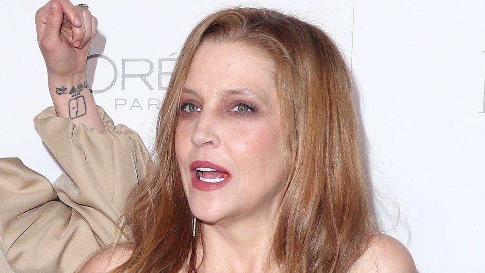 Lisa Marie Presley poses on the red carpet while speaking to her daughter, Riley Keough