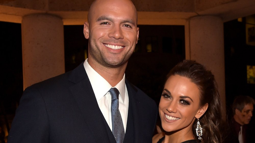 Mike Caussin in a blue blazer, Jana Kramer in a black dress, both smiling and holding each other