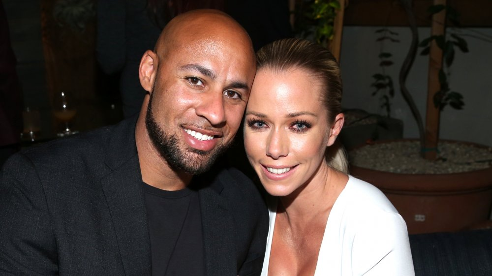 Hank Baskett in black, Kendra Wilkinson in white, both smiling while posing together