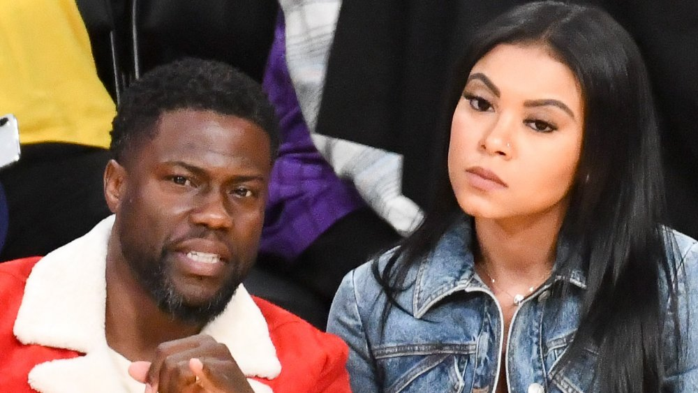 Kevin Hart in a red jacket, Eniko Parrish in a jean jacket, both with serious expressions