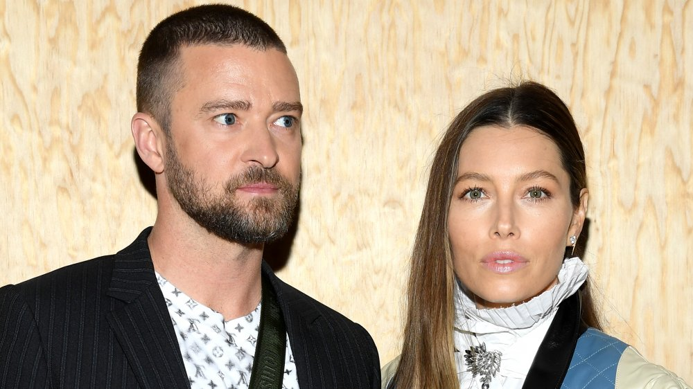 Justin Timberlake in a black-striped blazer and patterned white t-shirt, Jessica Biel in a white-and-blue outfit