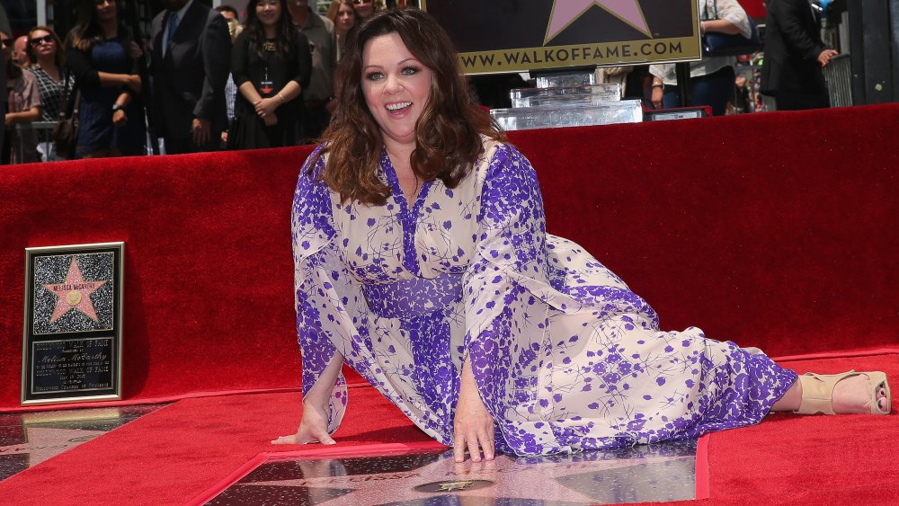 Melissa McCarthy sitting next to her star on the Hollywood Walk of Fame