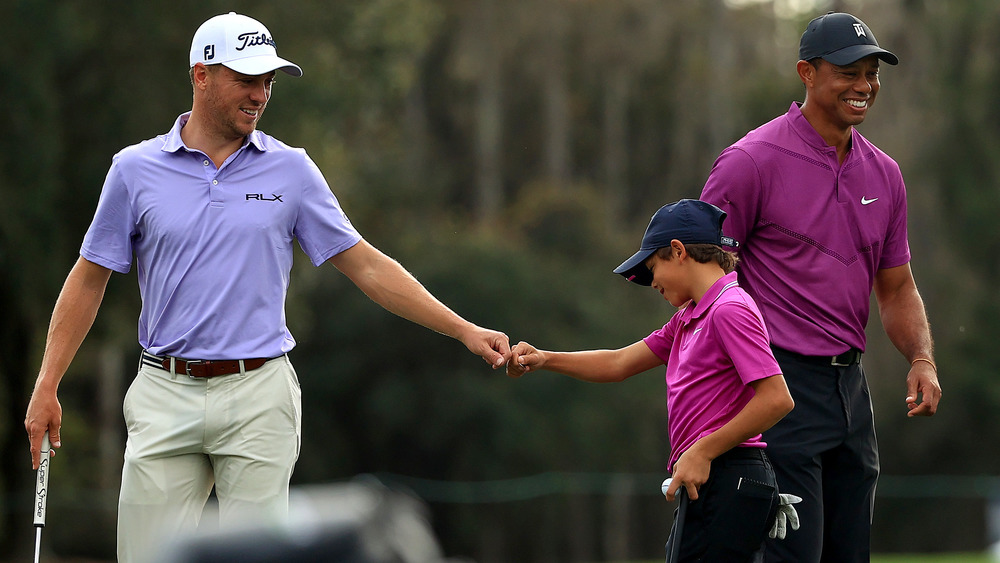 Justin Thomas with Charlie Woods and Tiger Woods