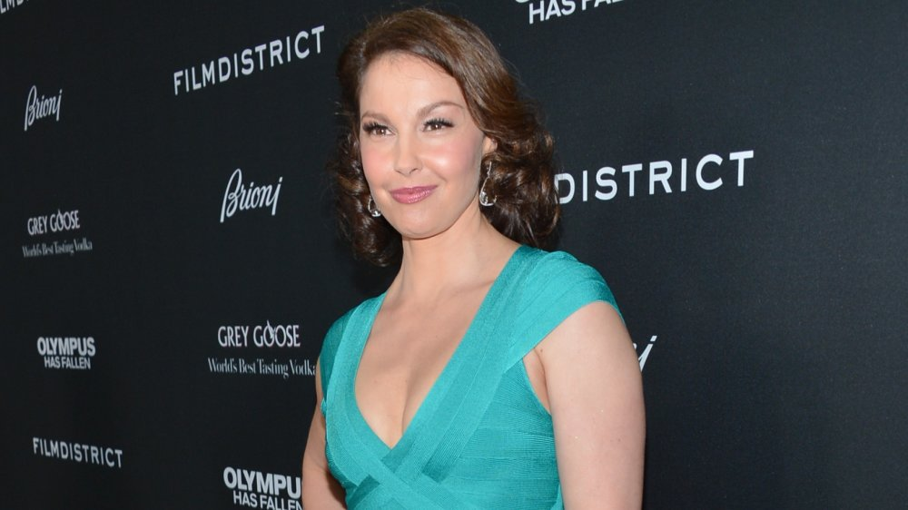 Ashley Judd in a teal dress, smirking and posing with one hand on her hip on the red carpet