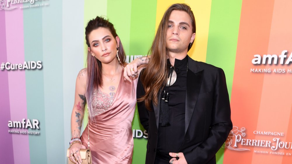 Paris Jackson and Gabriel Glenn posing together in front of #Cure AIDS wall